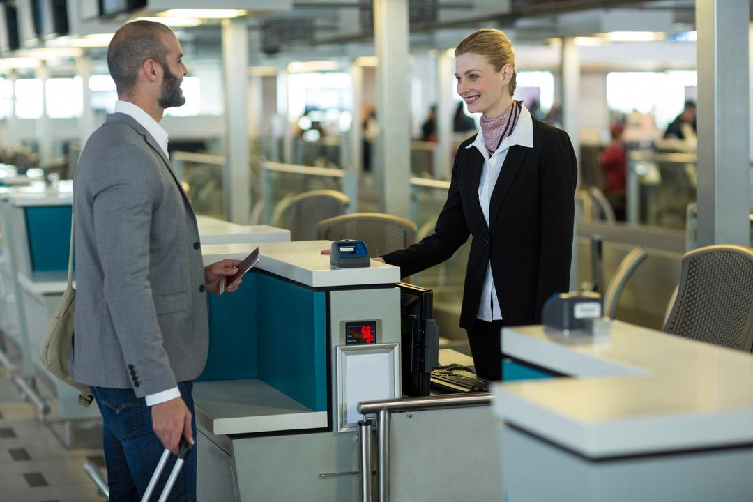 Smiling commuter interacting with attendant at check-in counter