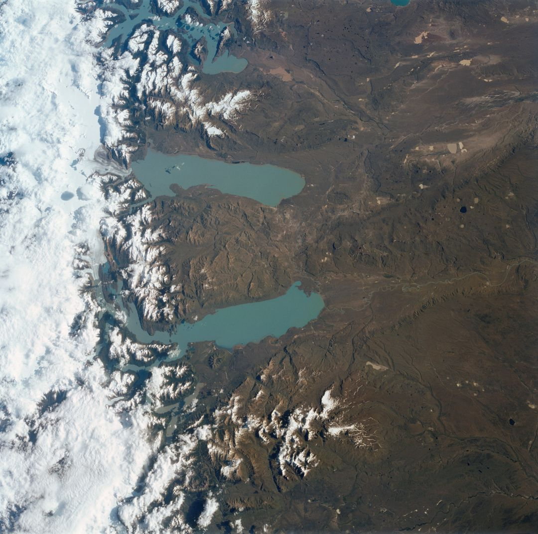 "STS113-708-014 (23 November - 7 December 2002) --- The STS-113 crewmembers used a handheld 70mm still camera to record this image of Patagonia lakes in southern Argentina.  The lowest of the three lakes in this view is Lake Argentino.  The next one north (middle lake) is Lake Viedma, and the lake on the top margin is Lake San Martín.  According to NASA scientists studying the STS-113 Earth imagery, all three of these large lakes have been carved out by glaciers in the ""recent"" ice age, descending from the Andes Mountains (under cloud along the right side of the view).  Three glacier tongues can be discerned as small white features leading into the western (left) ends of each lake.  The rounded ends of the lakes, according to the Johnson Space Center scientists, are produced by the slow ""flowing"" action of glacial ice on the plains next to the mountain chain.  Snow cap on lower peaks next to the cloud make a jagged pattern."