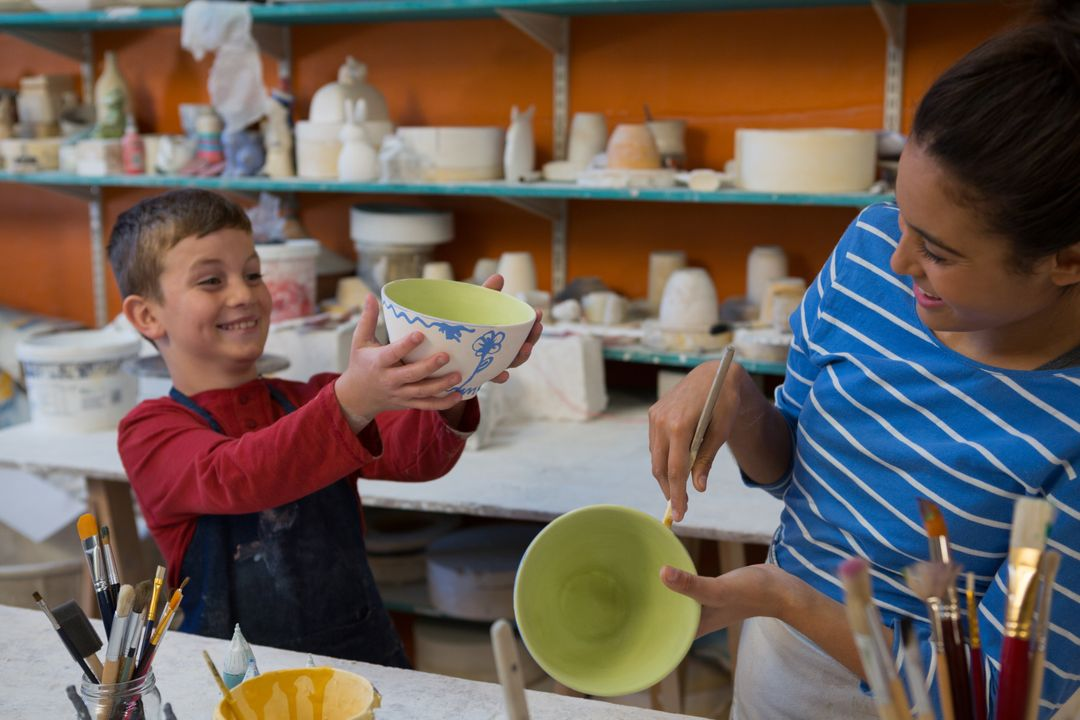 Female potter and boy painting bowl in pottery workshop Free Stock Images from PikWizard