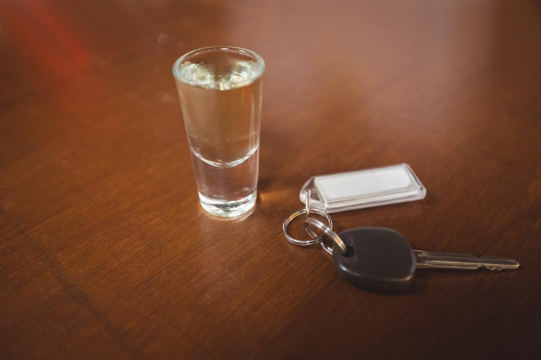 Glass of tequila shot with car key in bar counter at bar