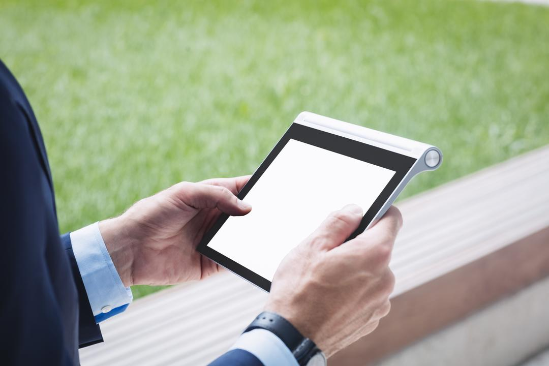 Close-up of a businessman using digital tablet outside office building Free Stock Images from PikWizard