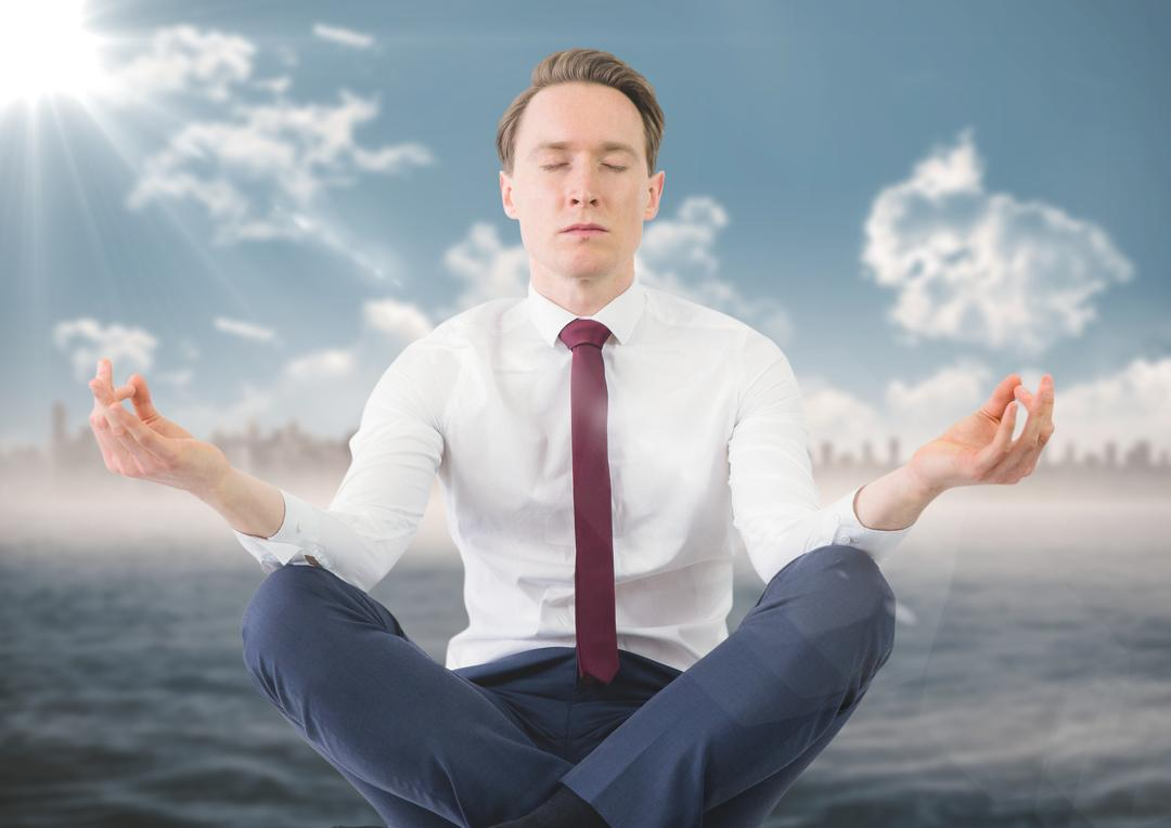 Digital composite of Business man meditating against water and blurry skyline with flare Free Stock Images from PikWizard