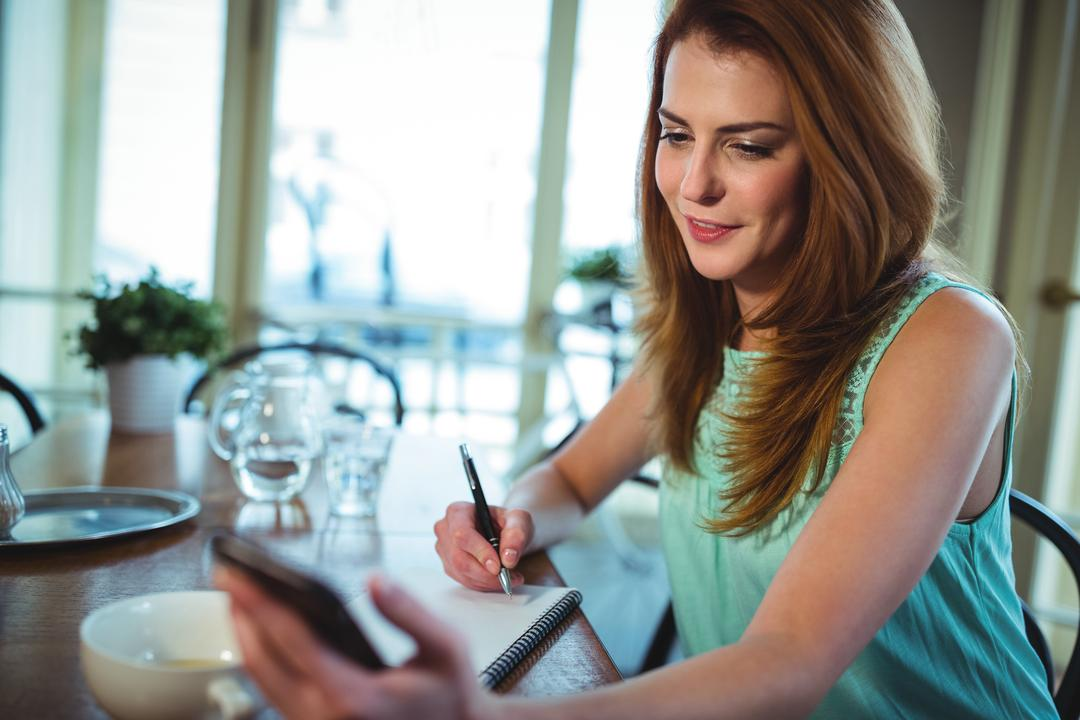Woman using mobile phone while writing on notepad