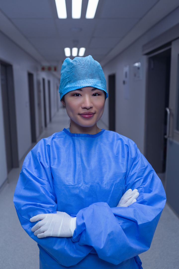 Front view of female surgeon with arm crossed standing in corridor at hospital