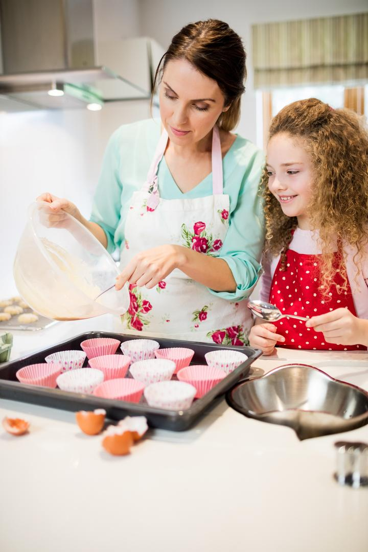Mother and daughter preparing cupcake in kitchen at home