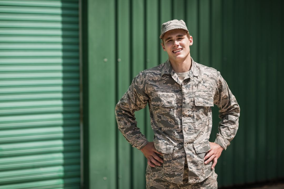 Portrait of smiling military soldier standing with hands on hip in boot camp Free Stock Images from PikWizard