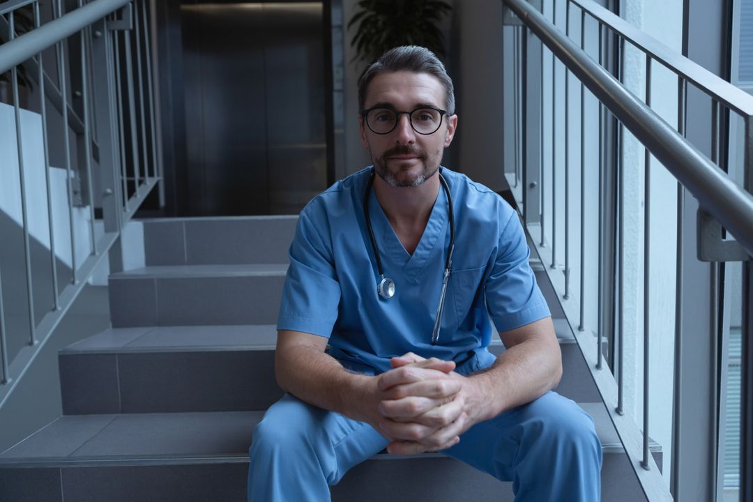 Front view of mature male surgeon looking at camera while sitting on stairs at hospital Free Stock Images from PikWizard