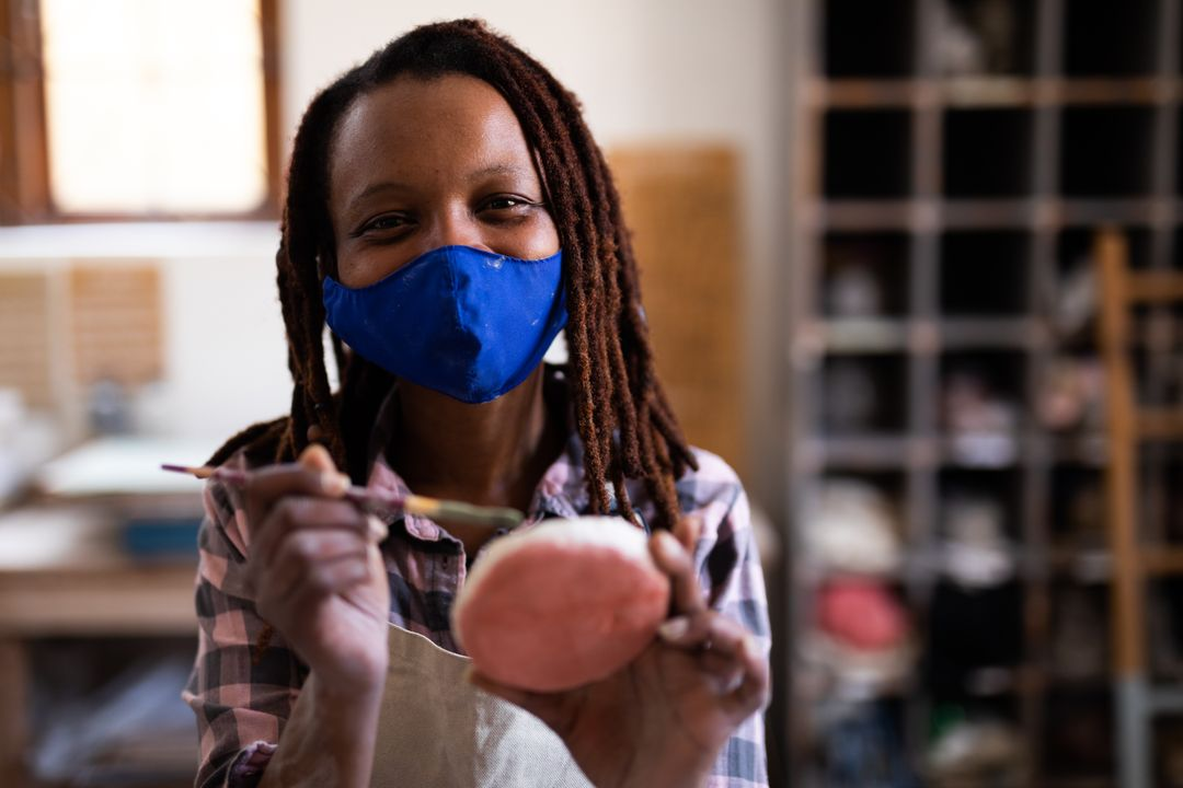 Mixed race female potter wearing face mask painting clay. Health and hygiene at pottery studio during coronavirus covid 19 pandemic. Free Stock Images from PikWizard