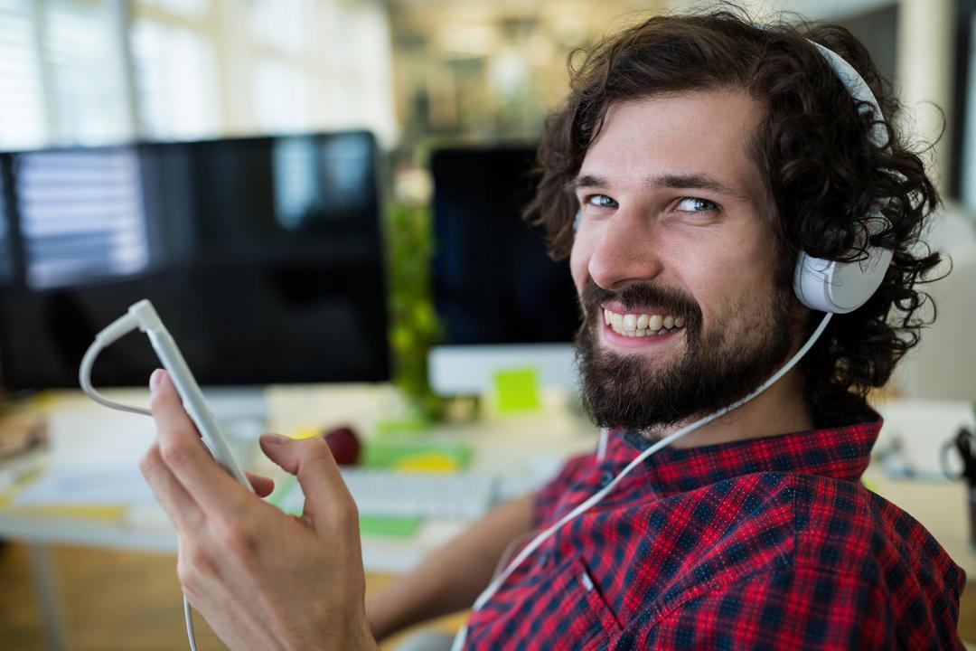 Male graphic designer listening music from mobile phone in office
