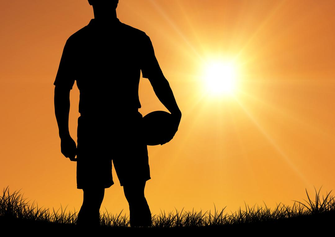 Silhouette of player holding rugby ball against sunset in background
