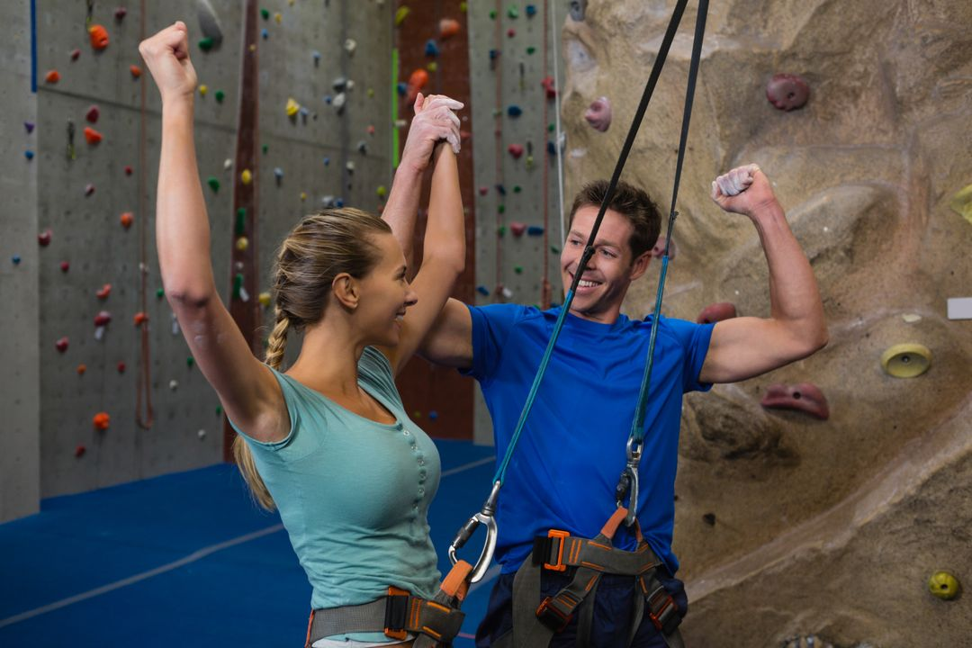 Cheerful athletes standing by climbing wall in fitness studio Free Stock Images from PikWizard