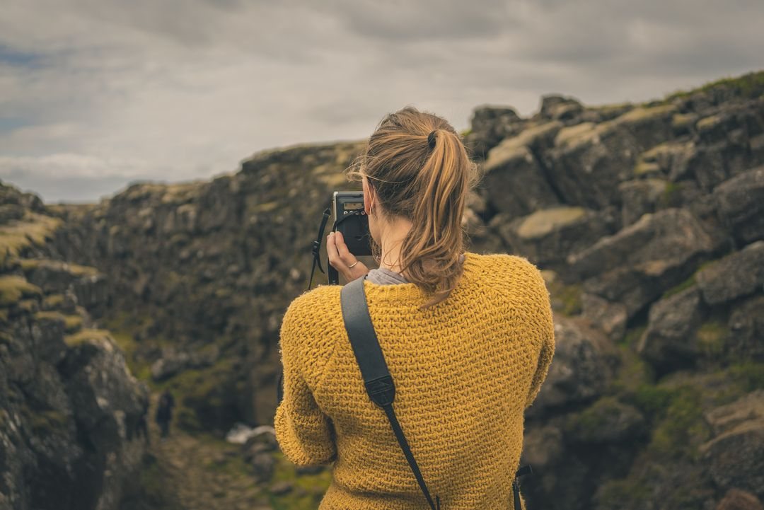 Woman in Yellow Knitted Sweater Taking Photo of Mountain during Day Time