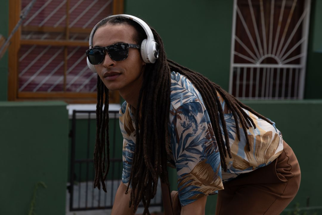 Mixed race alternative man with dreadlocks, sunglasses and headphones out and about in the city on a sunny day, riding bike. Urban trendy man on the go. Free Stock Images from PikWizard