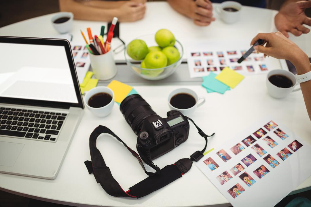 Image of a desk with a camera and laptop with people working on a project