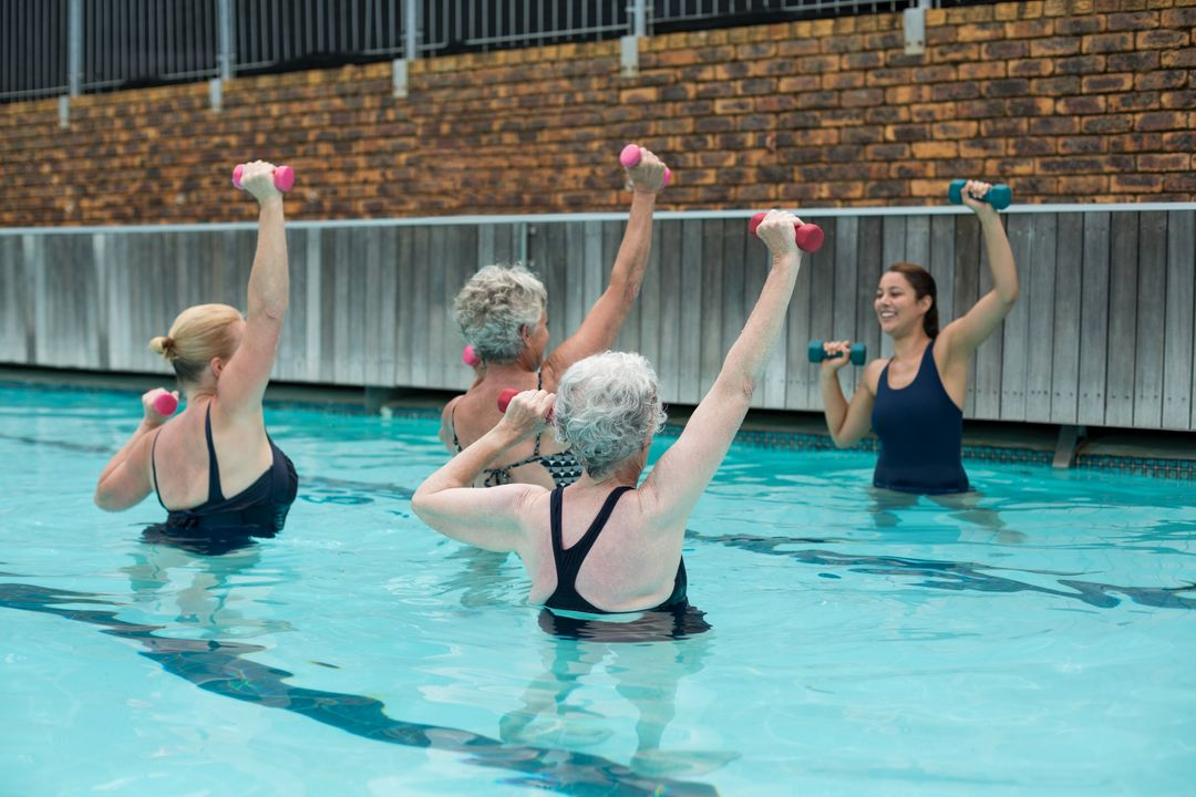 Trainer assisting senior women in weightlifting in swimming pool Free Stock Images from PikWizard
