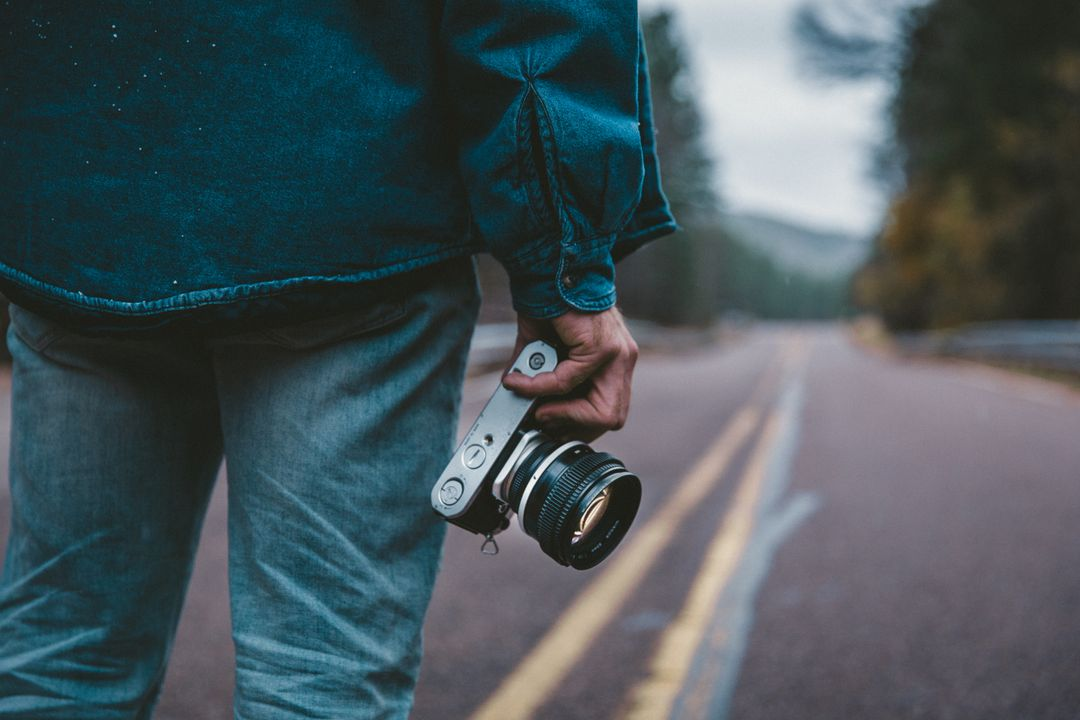 Man standing on road taking pictures