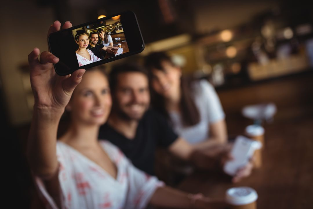 Friends taking a selfie on mobile phone at restaurant Free Stock Images from PikWizard