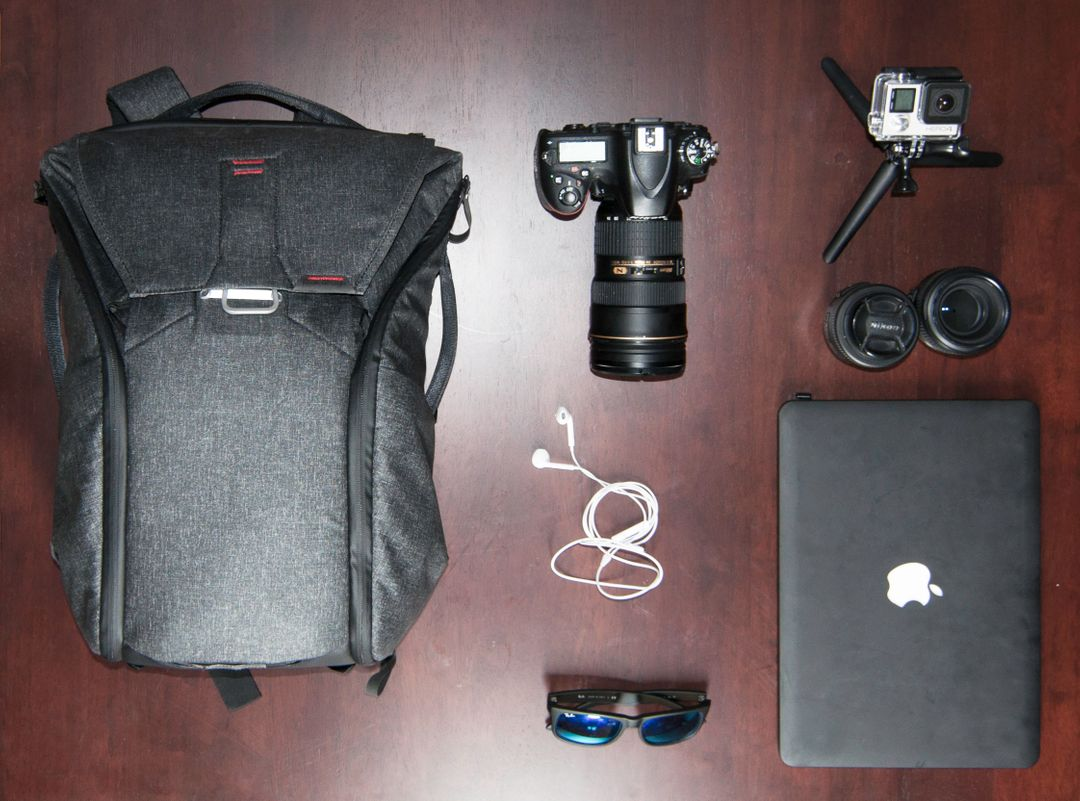 A photographer's kit including laptop, tripod, camera, rucksack on a table