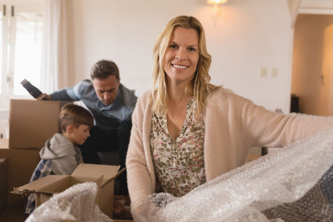 Portrait of happy mother smiling with her family in the background unpacking cardboard boxes in their new home Free Stock Images from PikWizard