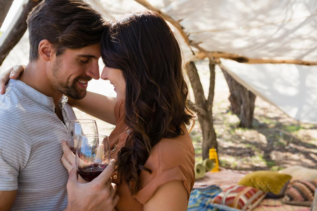 Romantic couple with wineglasses standing in tent