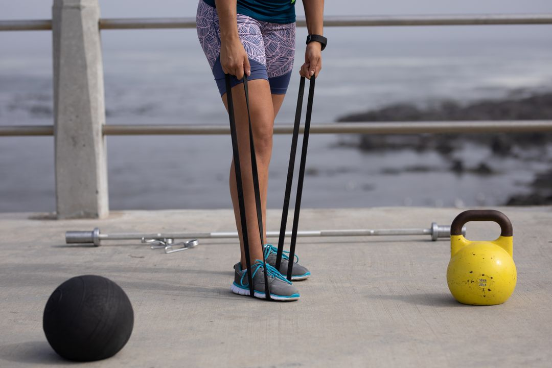 Front view low section of a strong Caucasian woman wearing sportswear exercising outdoors by the seaside on a sunny day, strength training holding black rubber tape with her foot and her hands, kettlebell and ball next to her..