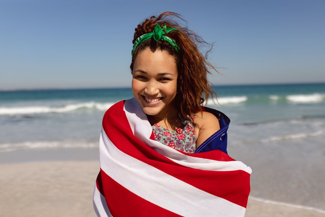 Portrait of beautiful young Mixed-race woman wrapped in american flag looking at camera on beach in the sunshine