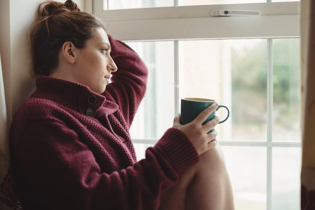 Thoughtful woman sitting at window sill and holding coffee cup at home
