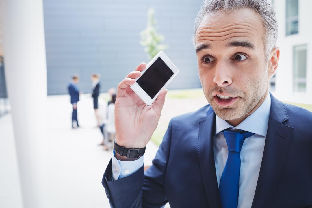 Businessman holding mobile phone and frowning outside office building