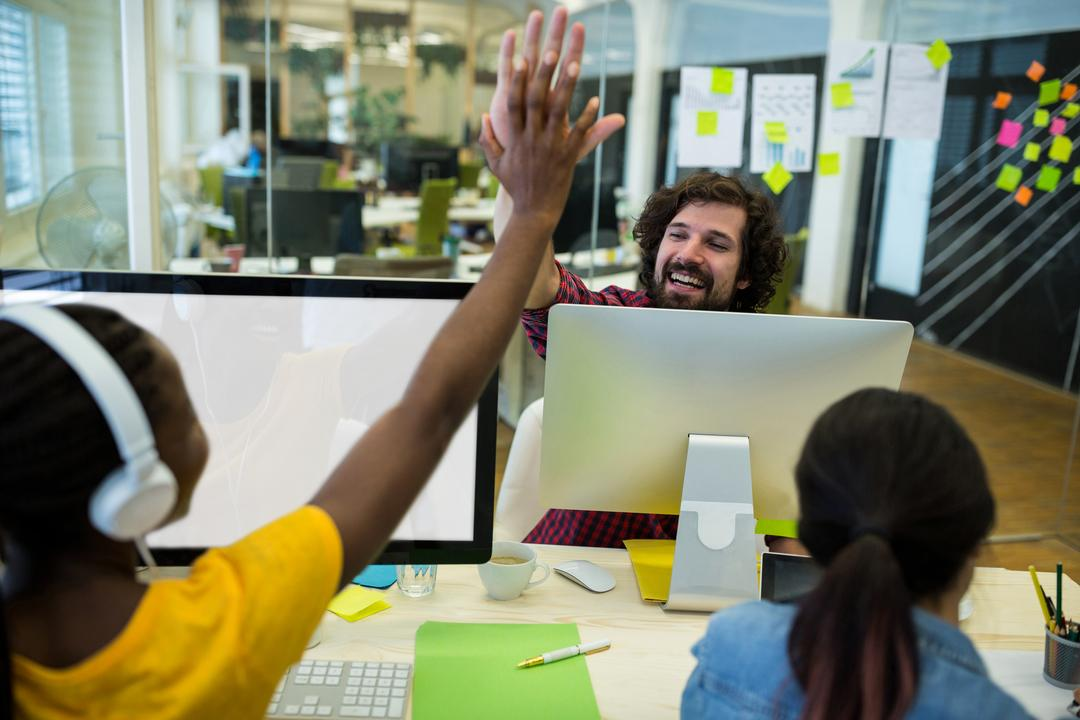 Male graphic designer giving high five to his coworker in office