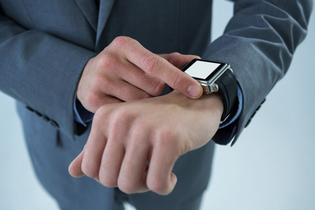 Mid section of businessman checking his smart watch Free Stock Images from PikWizard