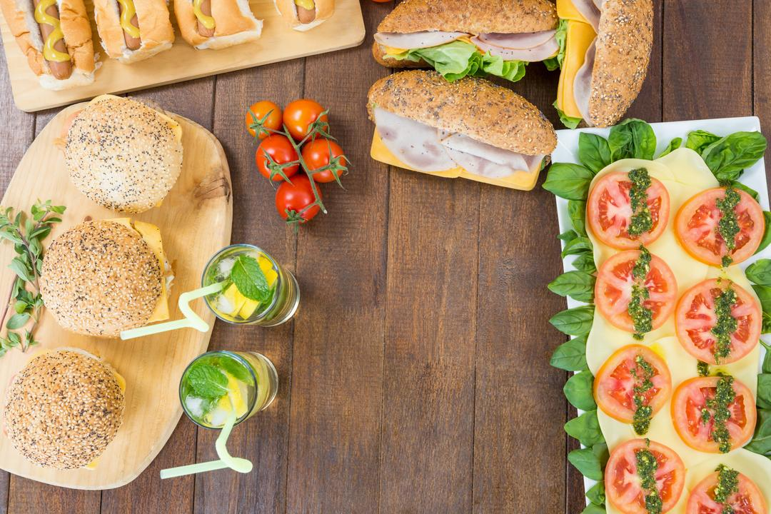 Salad, hot dogs, burgers and two glasses of mojito on wooden board