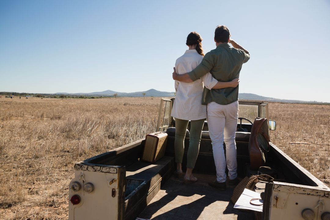 Rear view full length of young couple standing on off road vehicle at landscape