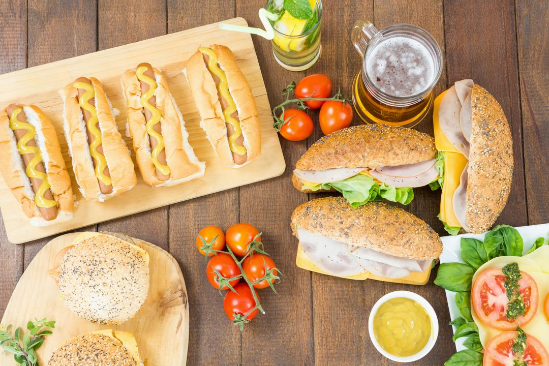 Salad, hot dogs, burgers, glass of mojito and beer on wooden board