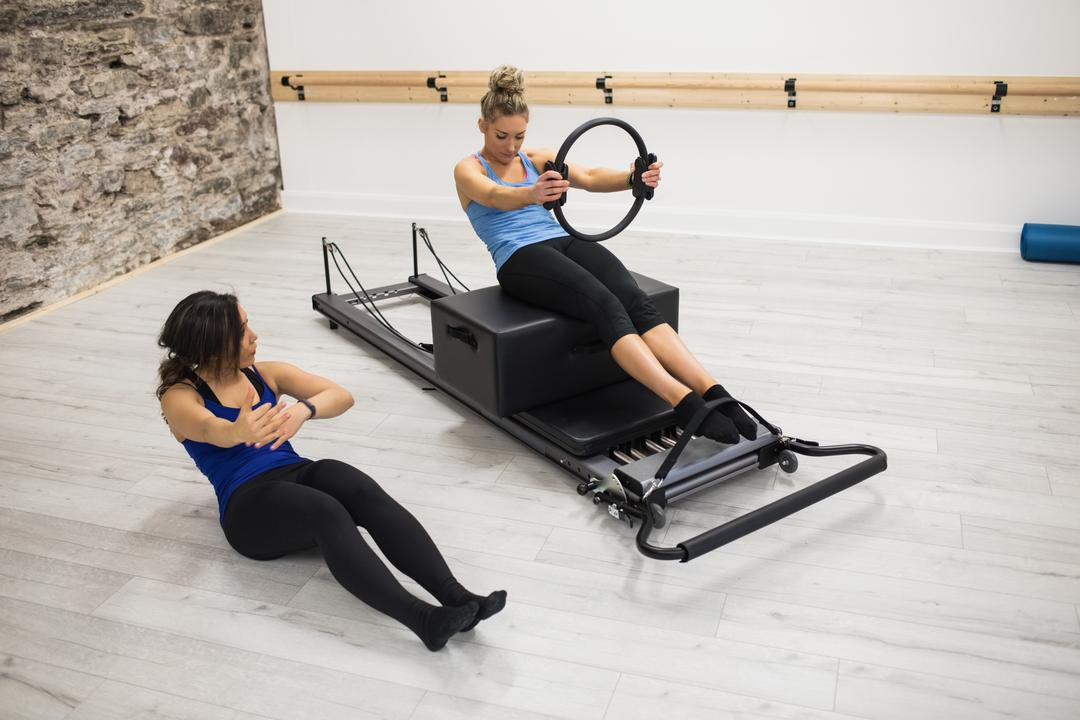 Female trainer assisting woman with exercising with pilates ring in gym
