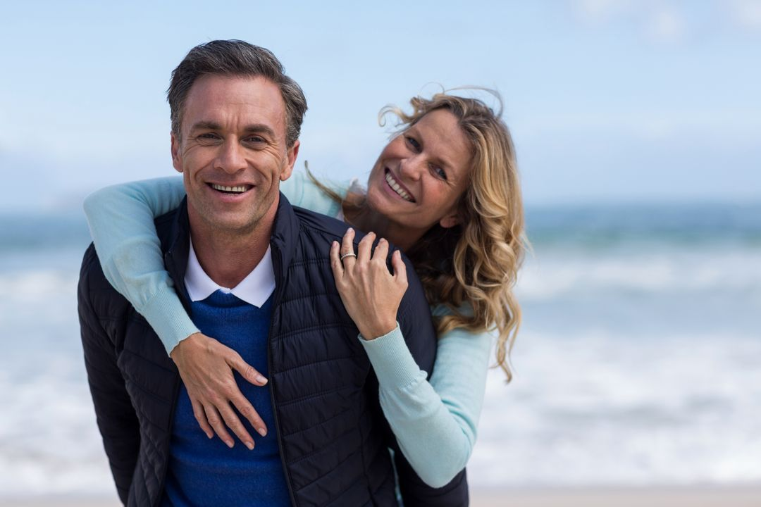 Portrait of mature man giving piggyback ride to woman on beach Free Stock Images from PikWizard