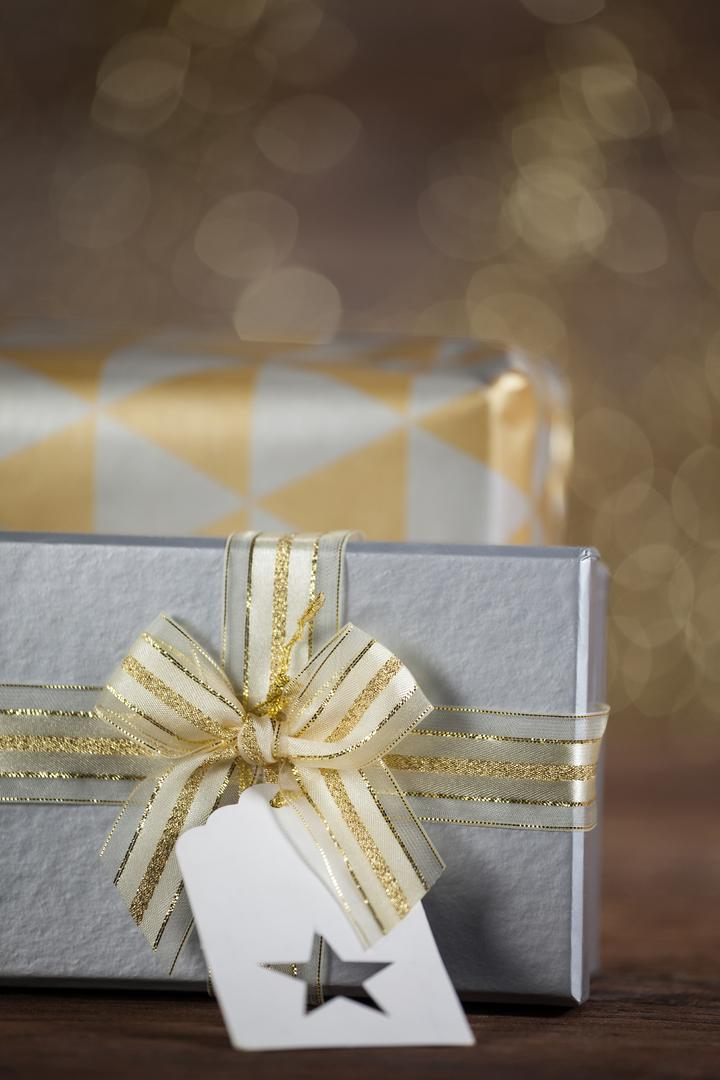 Close-up of wrapped gift box with tag on wooden table during christmas time