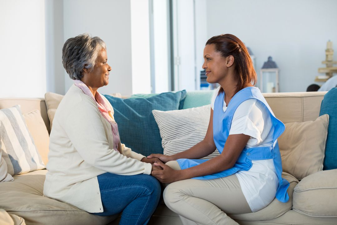 Female doctor comforting senior woman in living room at home Free Stock Images from PikWizard