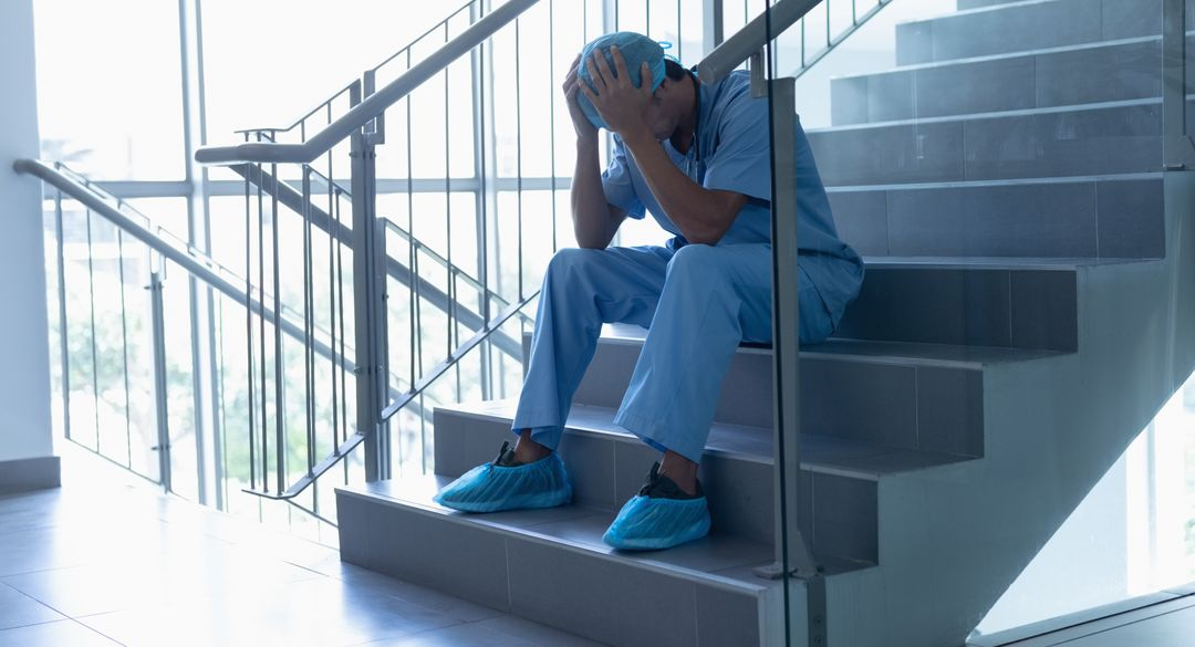 Worried male surgeon sitting on staircase in the hospital Free Stock Images from PikWizard