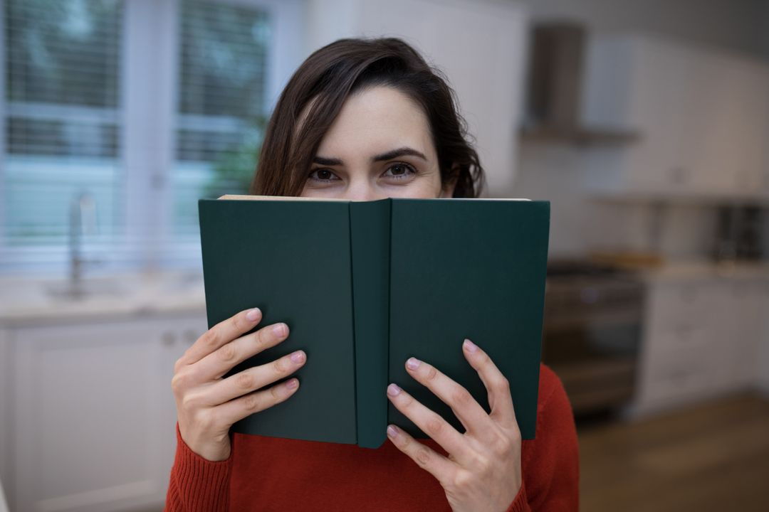 Portrait of beautiful woman covering her face with book Free Stock Images from PikWizard