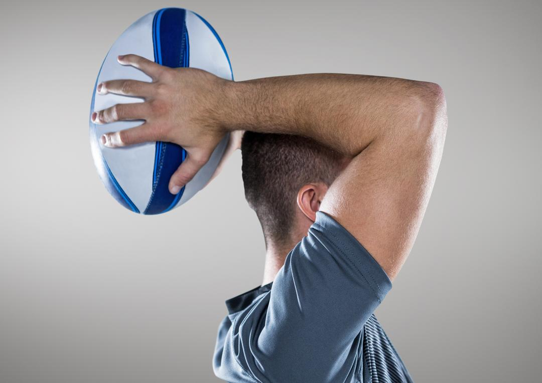 Side view of man holding rugby ball against grey background