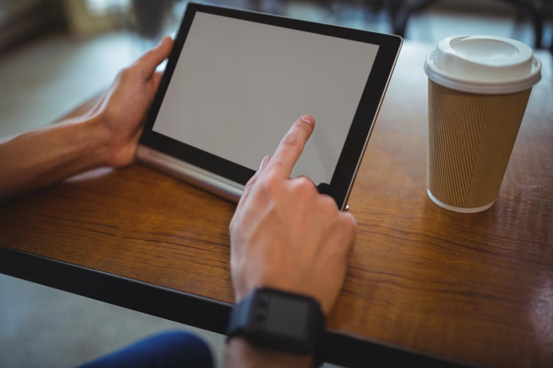 Man using digital tablet while having coffee in cafe Free Stock Images from PikWizard