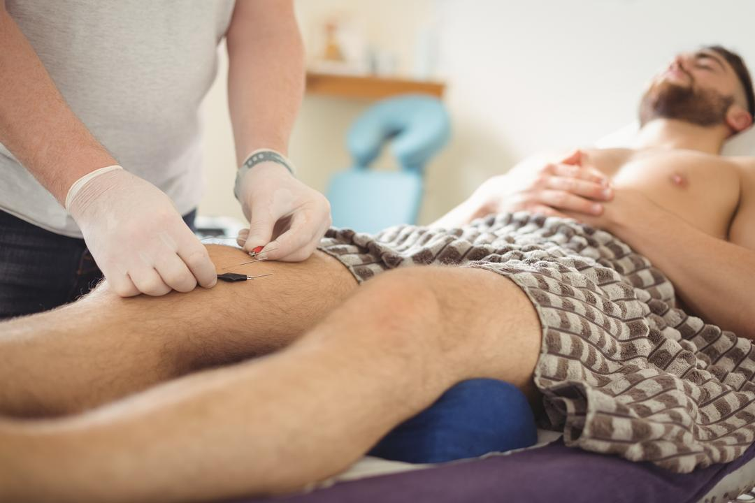 Physiotherapist performing electro dry needling on the knee of a patient in clinic Free Stock Images from PikWizard