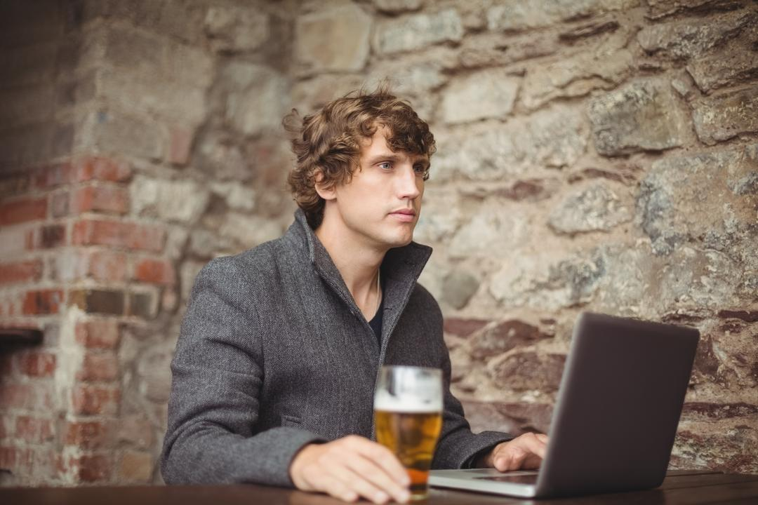 Close-up of man with glass of beer at bar