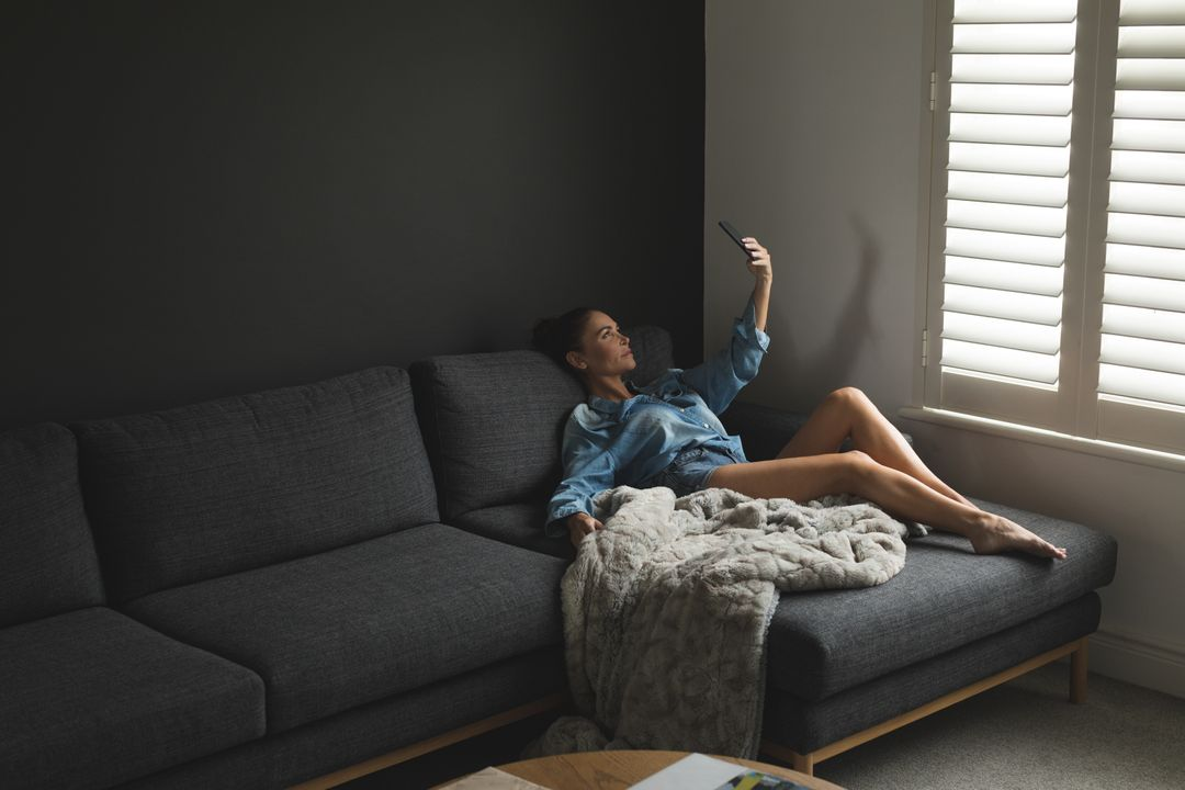 Beautiful woman taking selfie while relaxing on sofa in a comfortable home