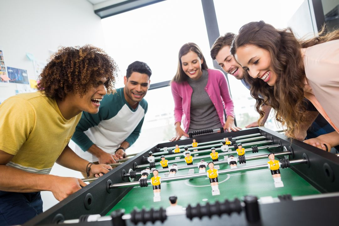 Happy executives playing table football in office Free Stock Images from PikWizard